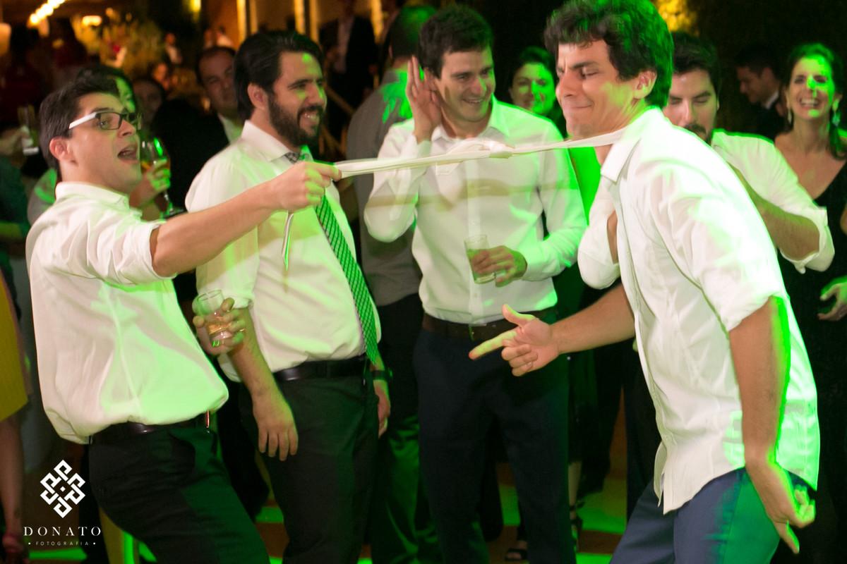 Padrinhos pegam e puxa a gravata do noivo.