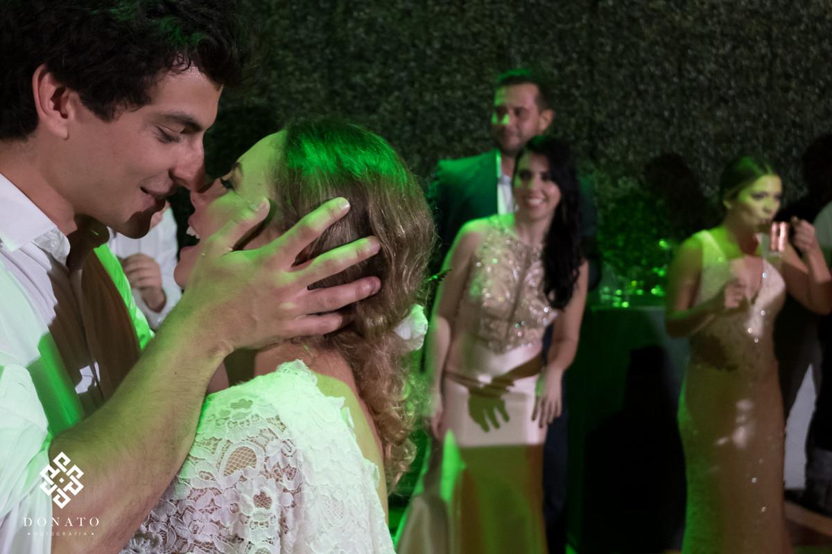 noivos se beijam na pista de dança.