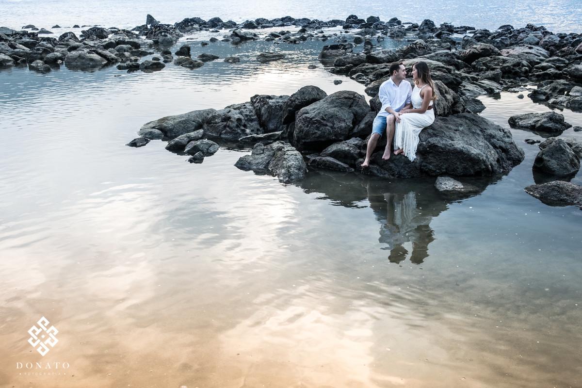 casal sentados em uma pedra linda rodeados do mar, com um lindo por do sol ao fundo.