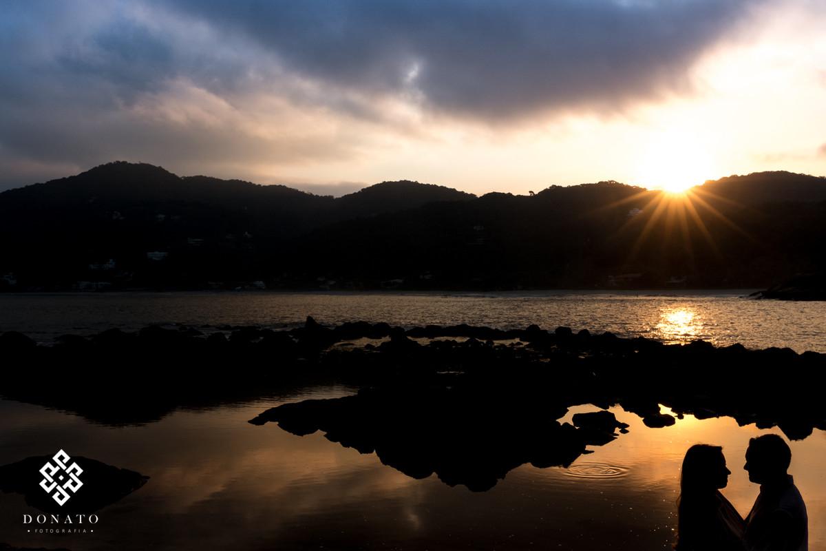 foto do lindo por do sol da praia do guaruja, com o mar ao fundo e com o casal e silheta todo escuro a frente.