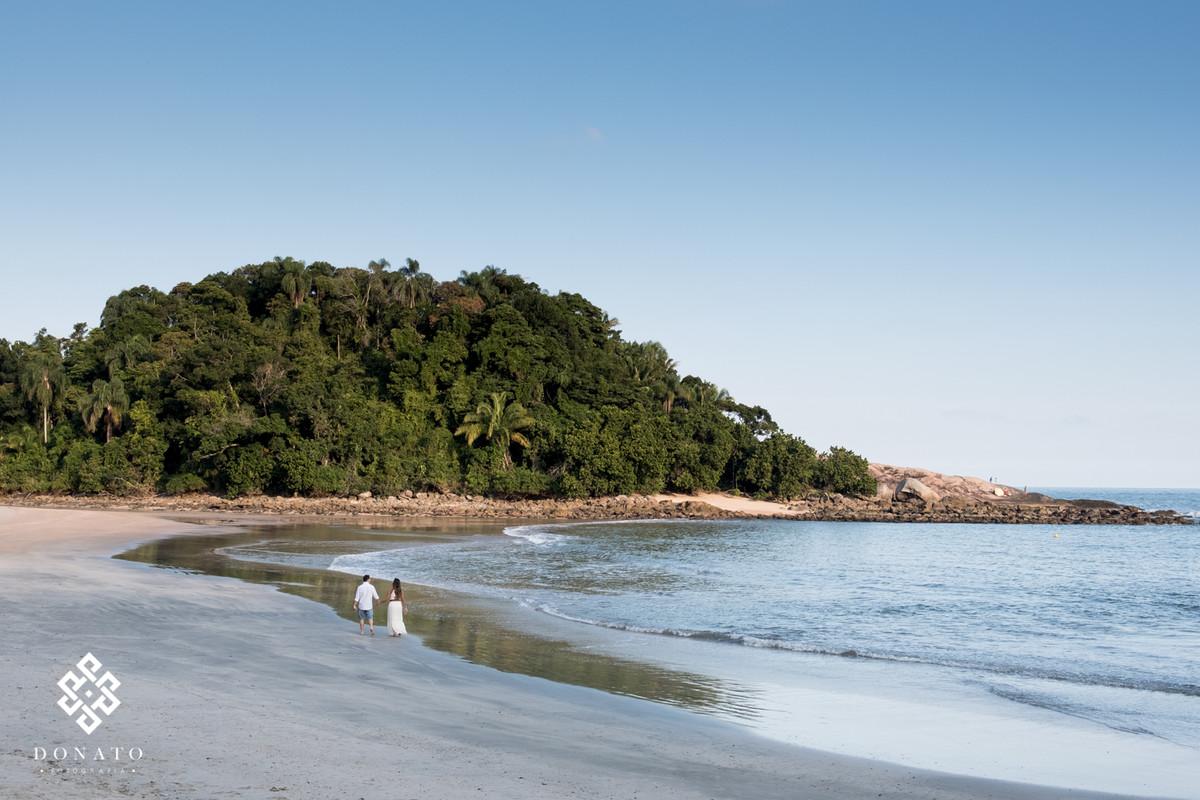 Visual da praia do guaruja - sp, onde o casal caminha a beira mar.