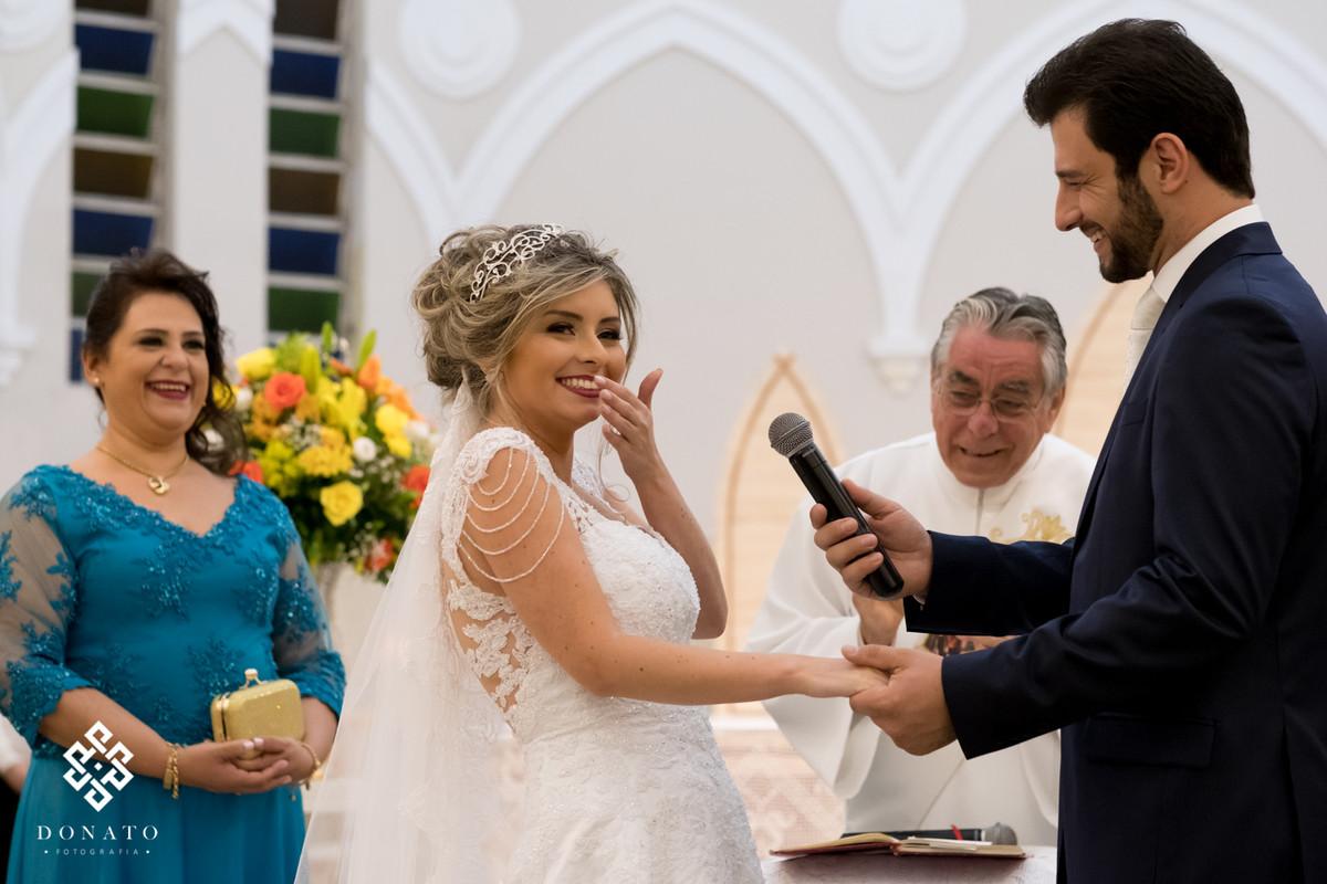 Noiva Jaqueline da um sorriso maroto, enquanto o noivo Mateus se declara a ela.