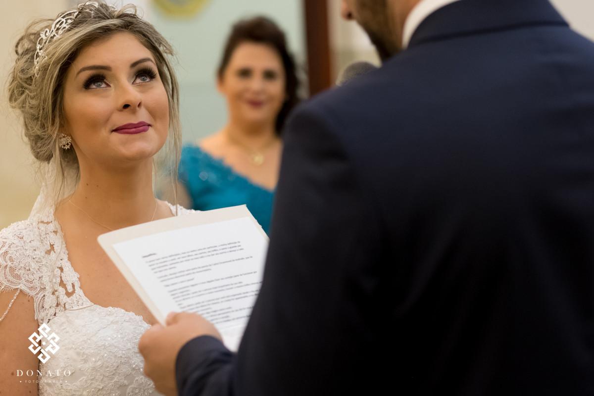 A noiva respira fundo para não chorar de eoção, enquanto o noivo Mateus lê seus votos.
