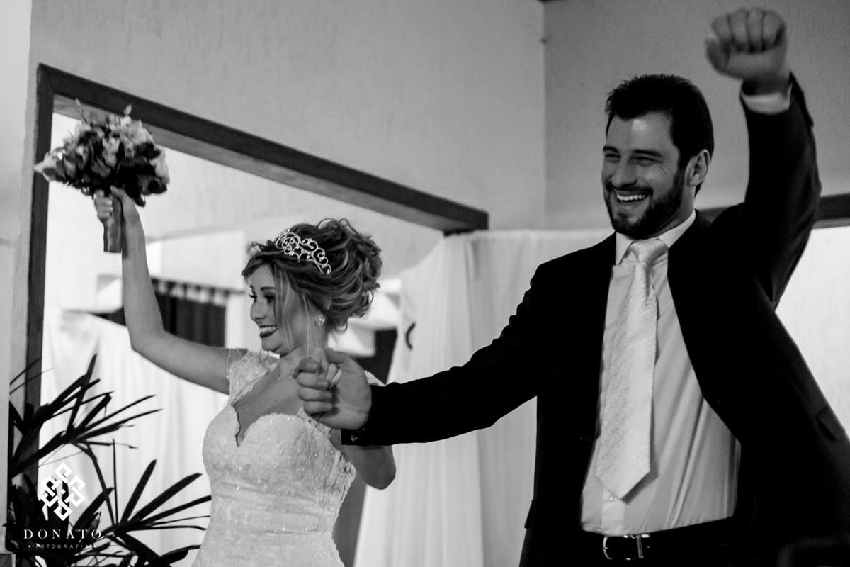 Noivos entram na festa de casamento comemorando
