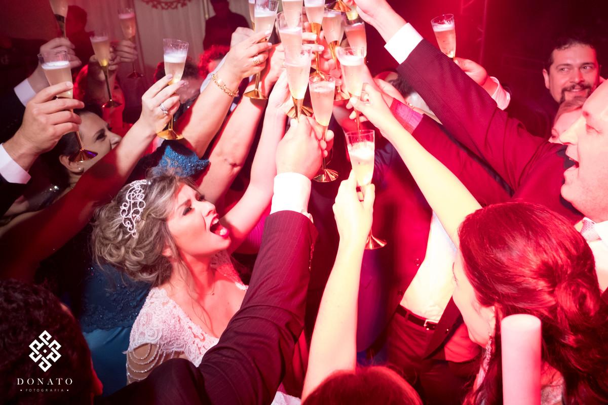 Noivos fazem um brinde com todos os padrinhos da festa.