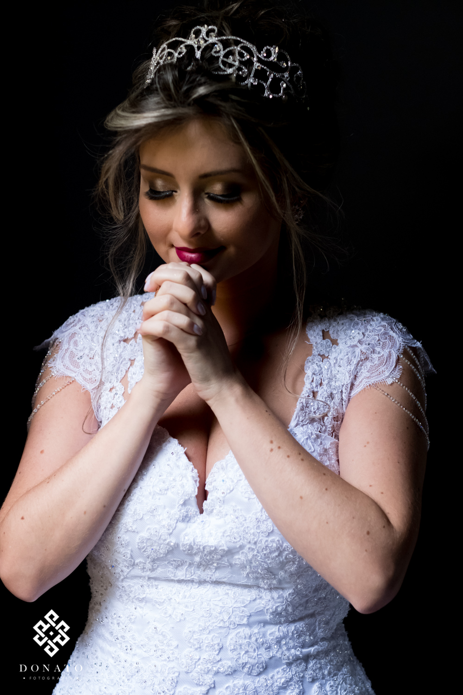 Noiva se concentra e reza antes da cerimonia, um lindo retrato da noiva com fundo preto.