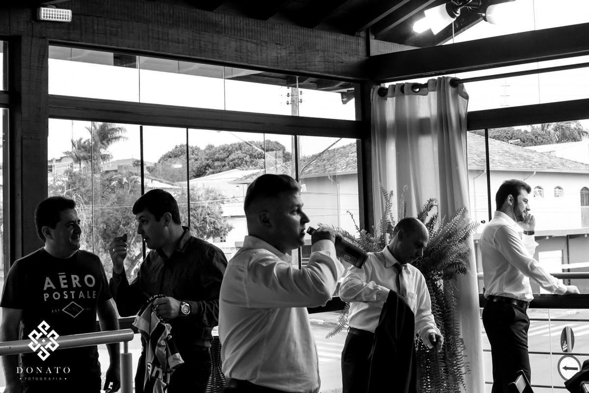 Noivo toma uma cerveja com os padrinhos antes do casamento.