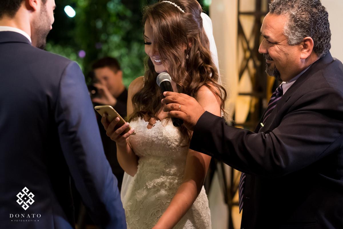 Noiva le os votos ao noivo que fica emocionado.