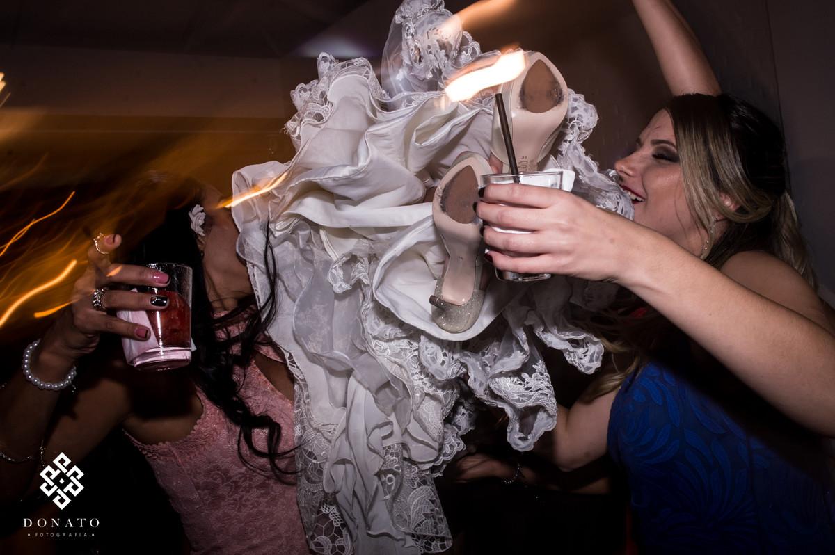 Amigas jogam a noiva para o alto no meio da festa.
