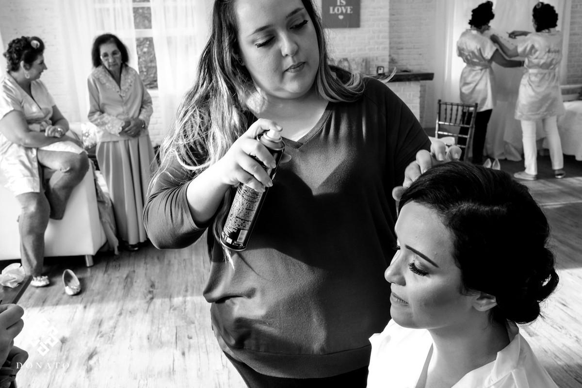 a maquiadora Tassya Lopes, finaliza o cabelo e a maquiagem da noiva.