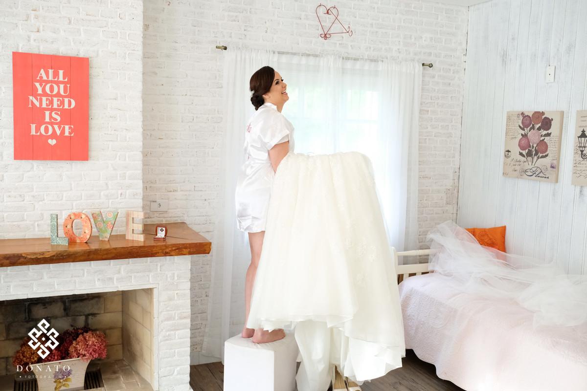 Noiva pega seu vestido Shophia Tolli para se vestir para o casamento.