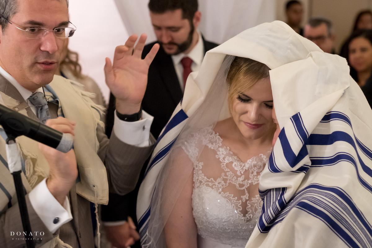 Noivos são coberto em um dos rituais da cerimonia judaica.