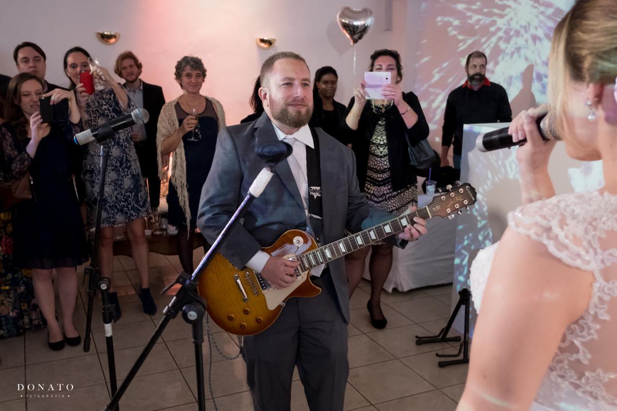 Noivo tocando sua guitarra na festa.
