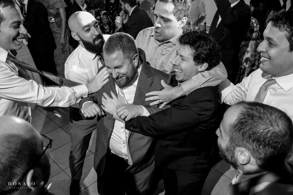 Convidados agarram o noivo, em um das tradiçoes do casamento judeu.