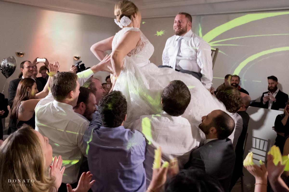 A noiva e o noivo são erguidos em cadeiras com é uma tradição nos casamento judaicos.