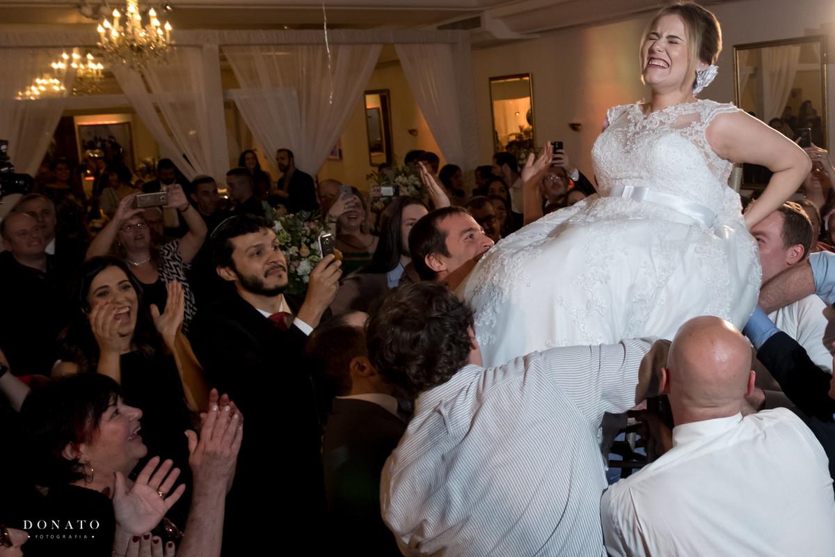 A noiva é erguida na cadeira com é uma tradição nos casamento judaicos.