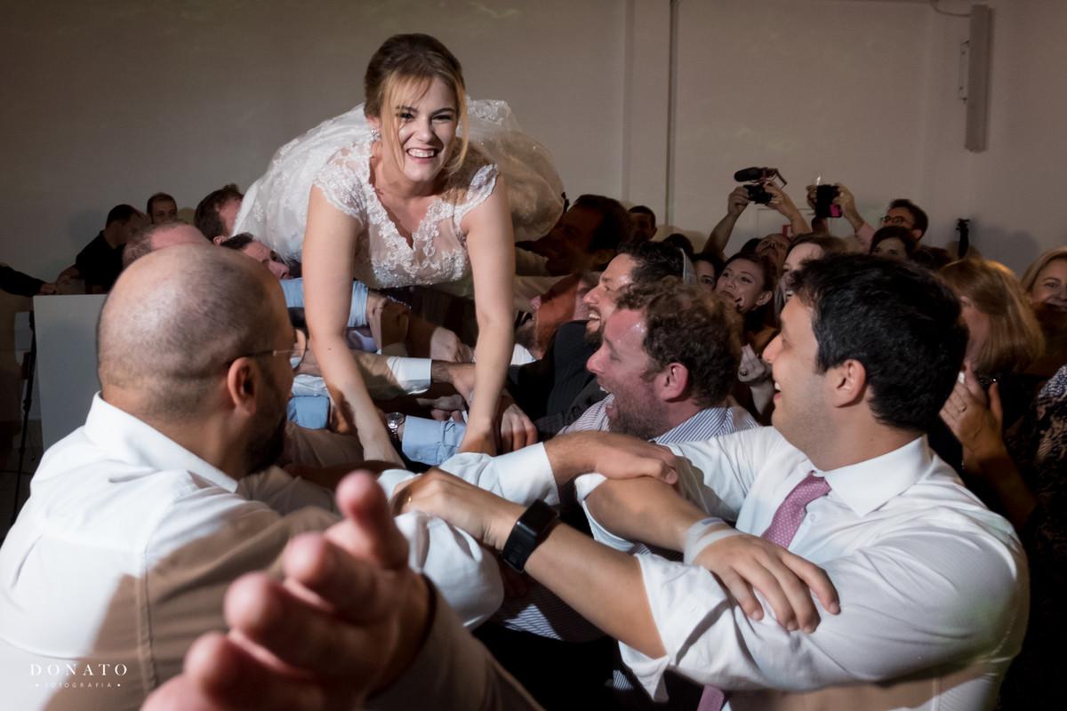 A noiva é jogada para o alto pelos padrinhos e amigos.