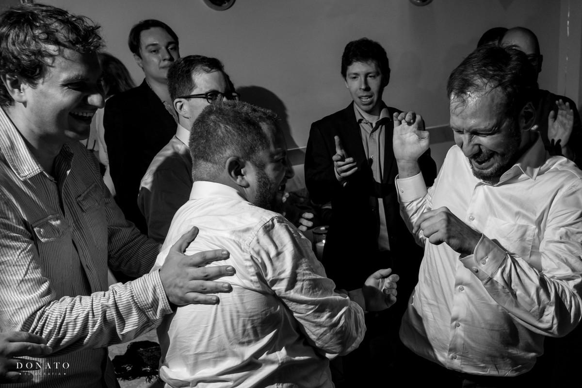 Amigos agarram e batem carinhosamento no noivo em um dos rituais do casamento judeu.