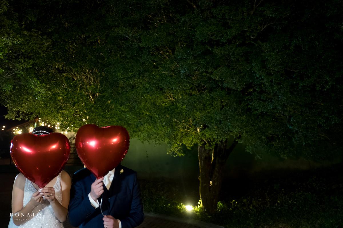 Noivos fazem foto com balão no jardim do sitio sao jorge
