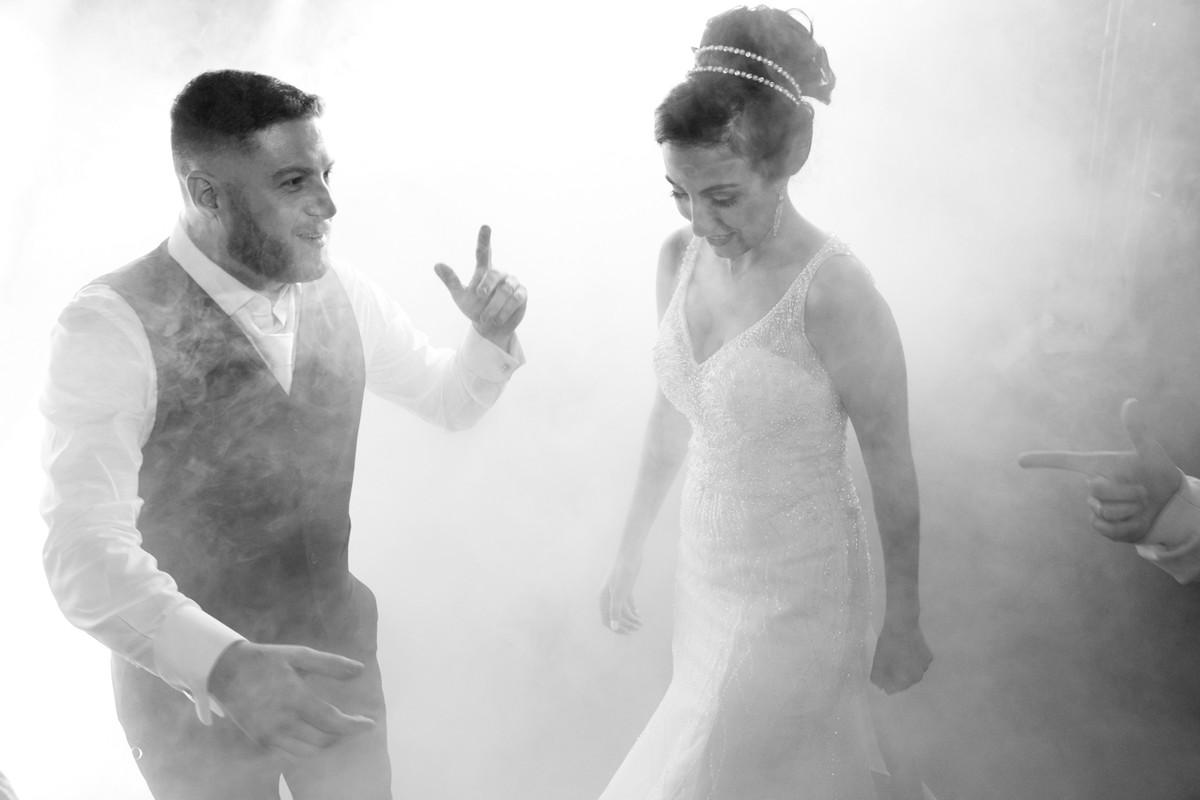 Noivo e noiva envolte de fumcaça na pista de dança.