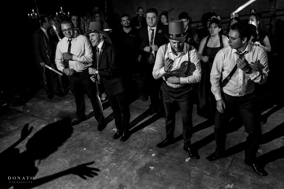 Noivo e amigos dançam, enquanto uma sombra dança junto com eles.