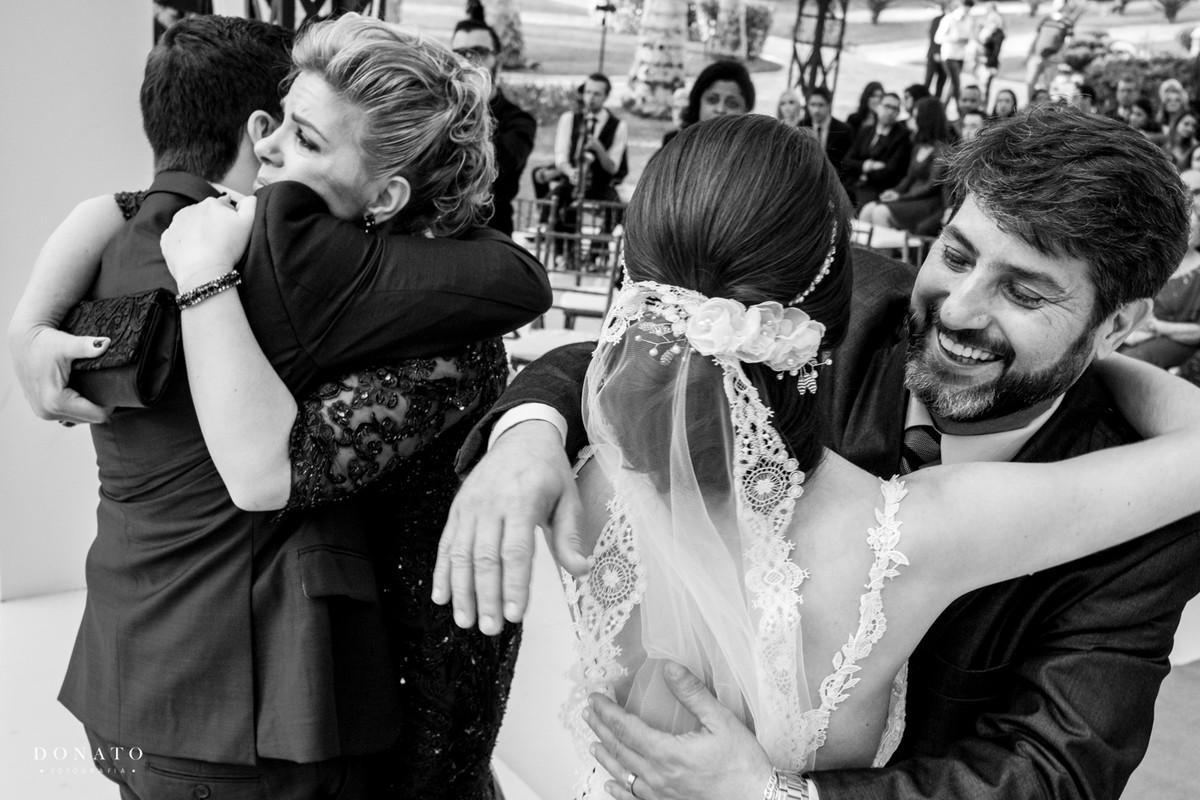 pais abraçam a noiva.
