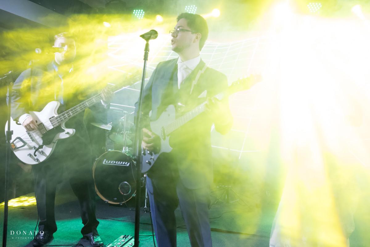 noivo toca guitarra em seu casamento.