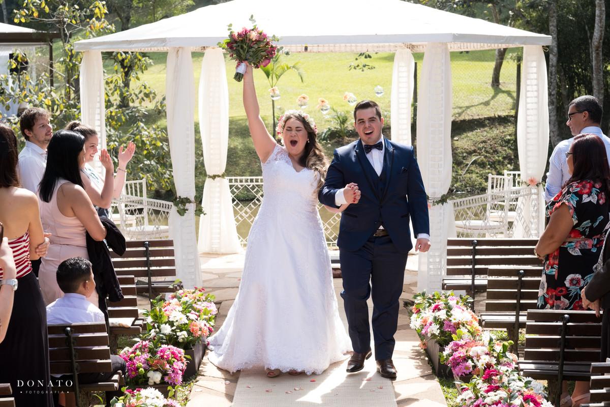 Noiva e noivo saem da cerimonia do espaço natureza em um lindo dia de sol.