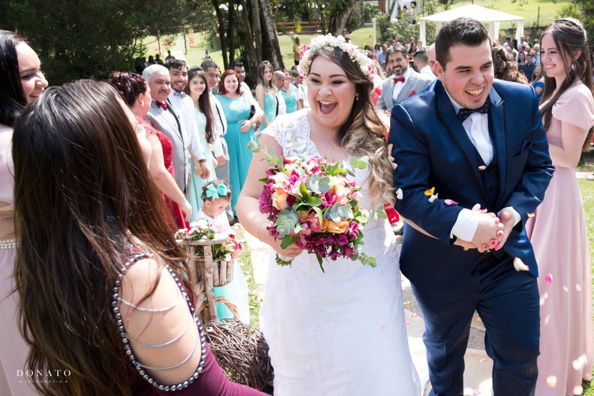 Noivo e noiva saem e recebem uma linda chuva de petalas, em meio a natureza e arvores.