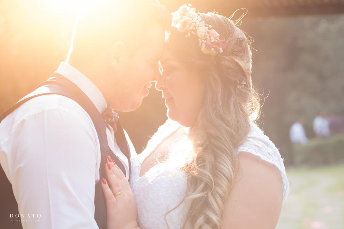 Foto dos noivos no final da festa com um lindo por do sol.