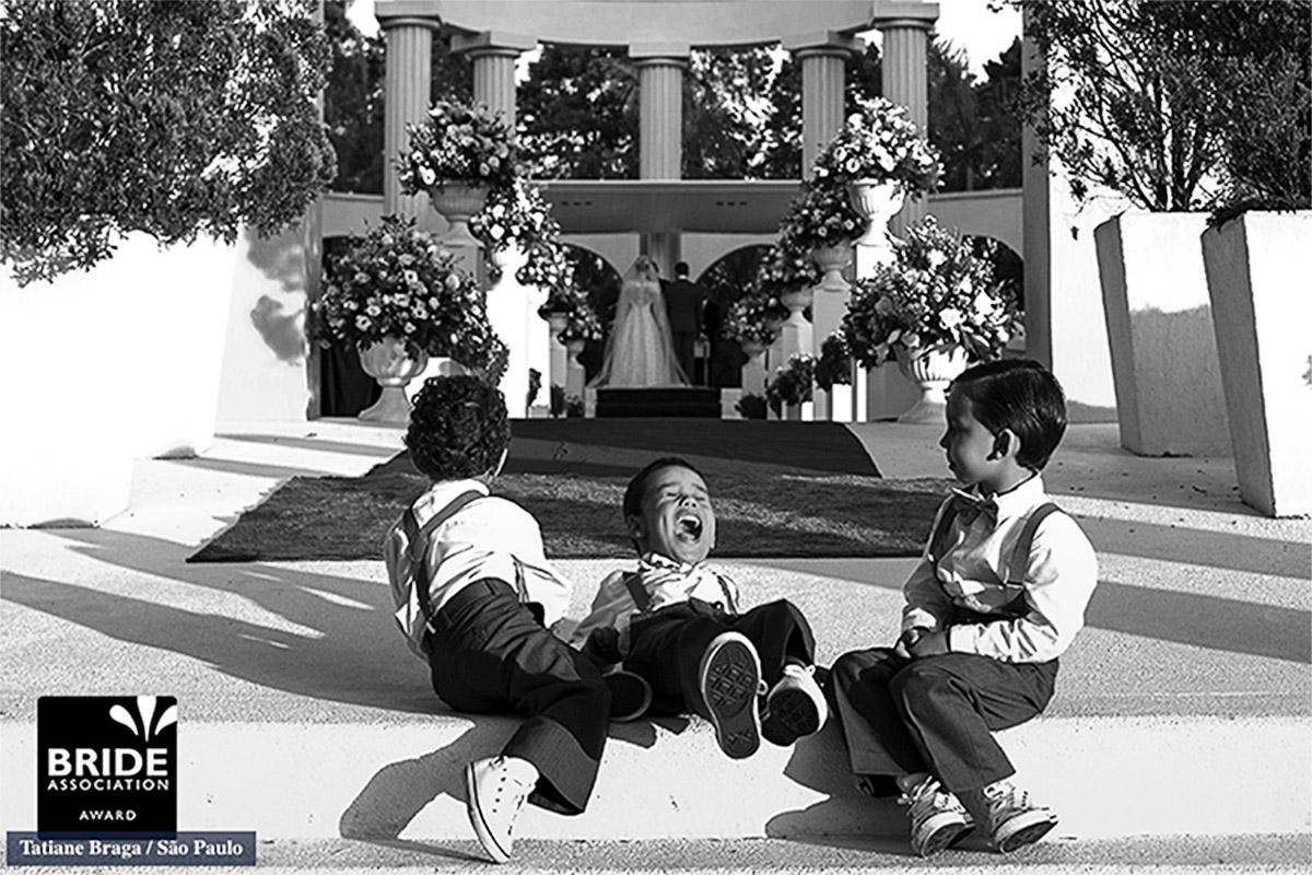 Fotos das crianças se divertindo ao fundo da cerimonia, um lindo sorriso do menino que esta ente outros dois garotos faz com que esta imagem seja forte e alegre, a foto foi premiada mais de 4 vezes.