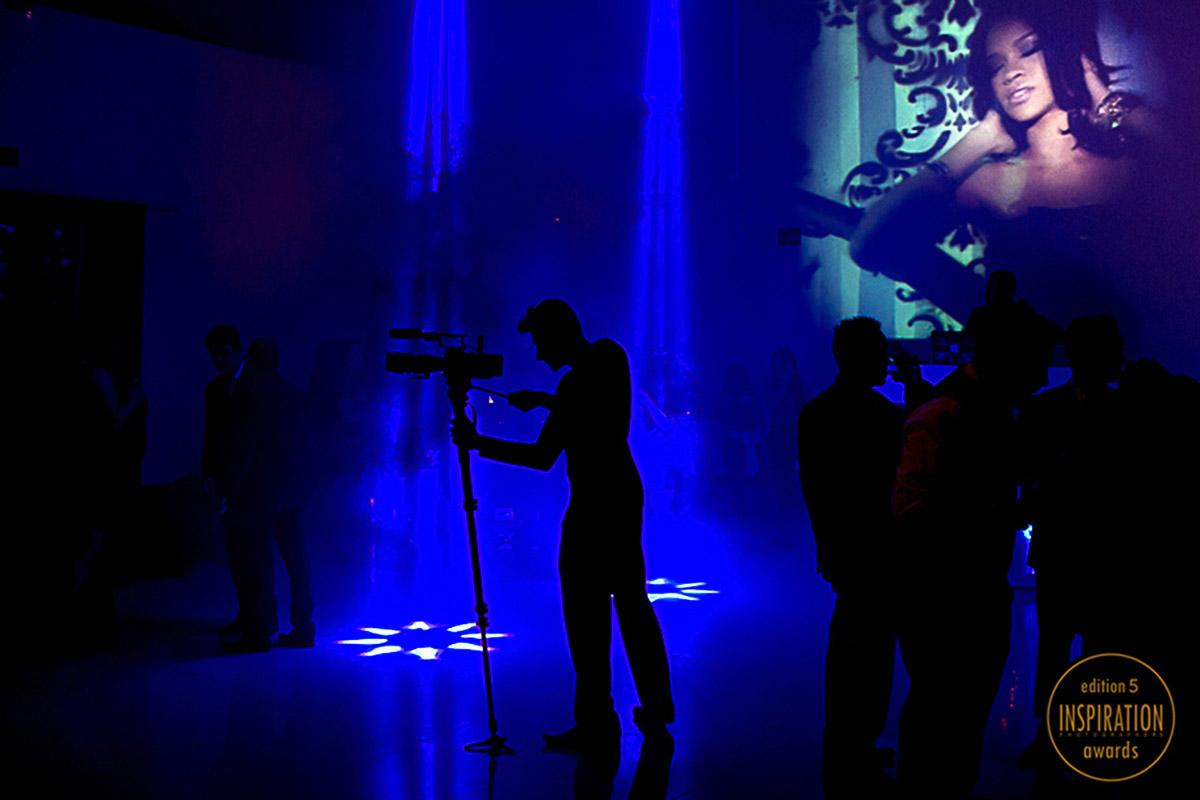 Foto do camera trabalhando com sua camera, a imagem é uma silhueta toda preta em meio a um fundo muito azul das luzes da balada, a foto teve o premio no inspirations em 2014.