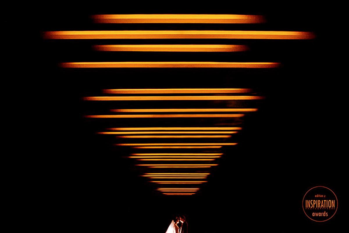 Foto de um casal minimal, linhas laranjas levam o olhar até o casal, deixando a imagem forte e criativa, foto premiada em tres concursos consecutivamente.