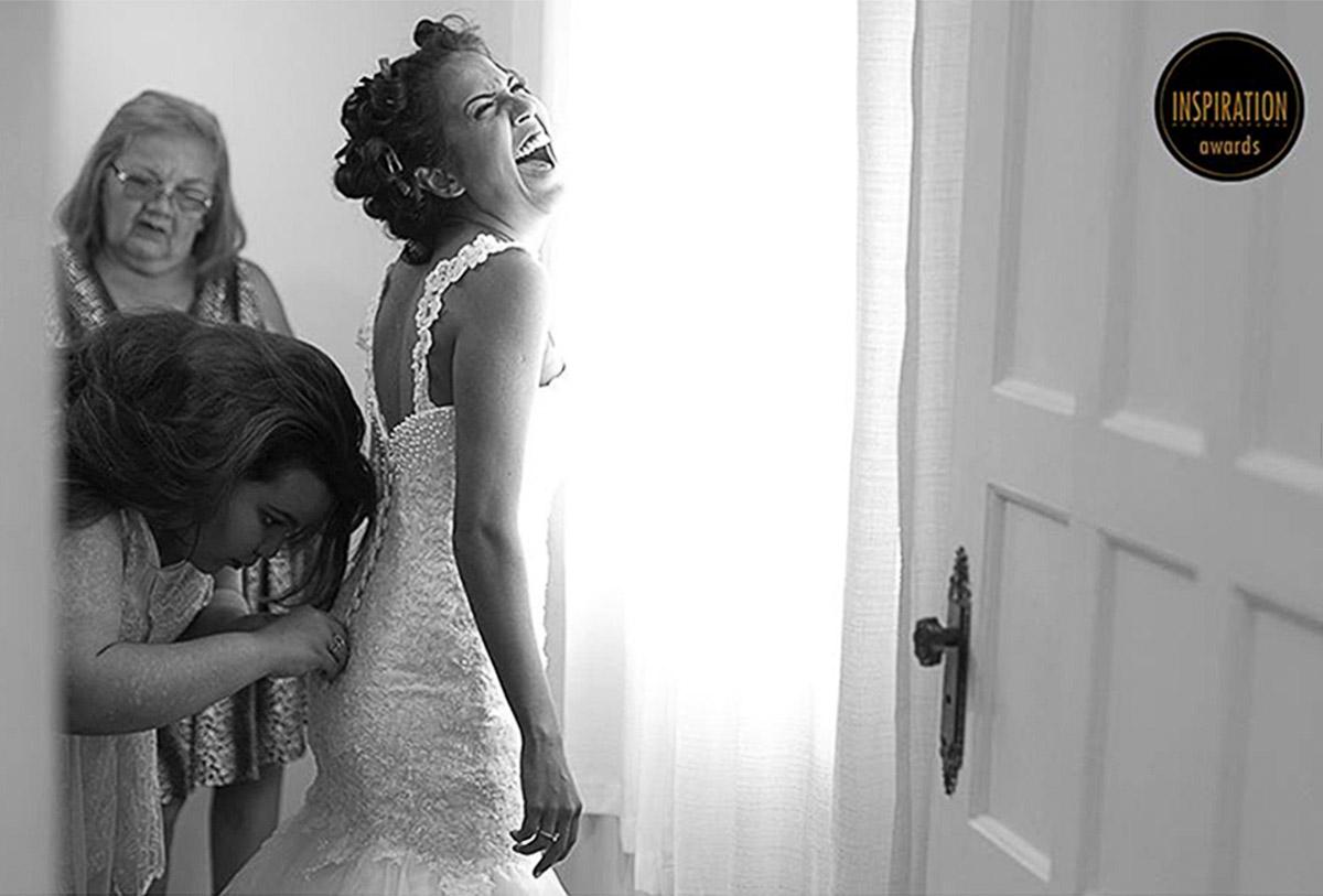 Noiva solta um lindo soffriso enguato a irmã aperta seu vestido com força, a luz é incrivel e suave, a foto ganhou alguns prêmios na categoria casamento.