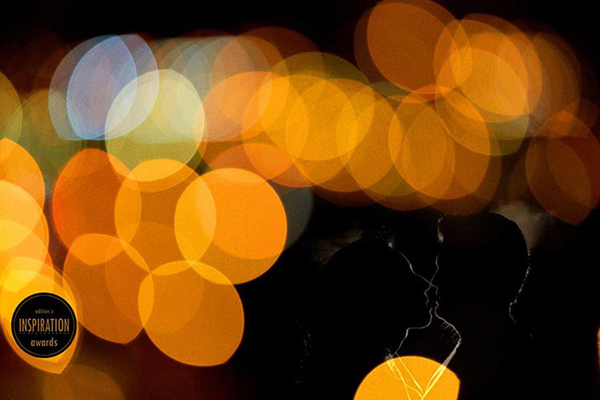 Leve contorno do casal entre uma serie de luzes laranja, a foto é muito criativa e também foi premiada algumas vezes.