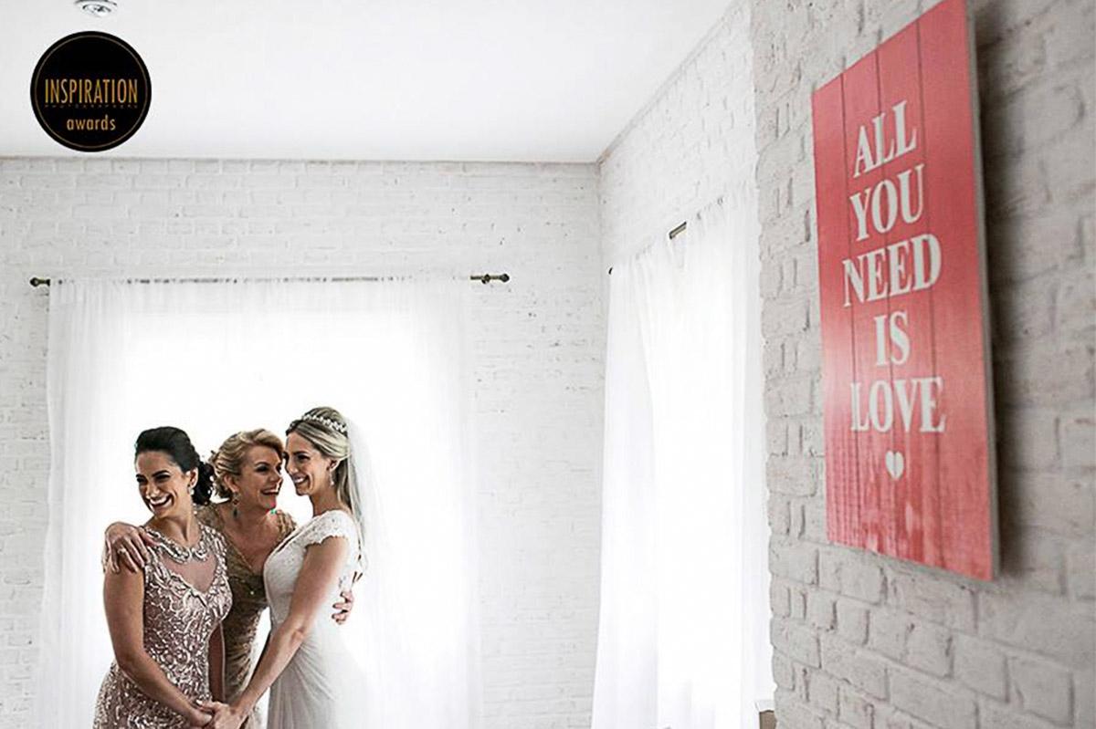 Momento unico da noiva com a mae e irmã, na composição tem uma placa dizendo All Need is Love.