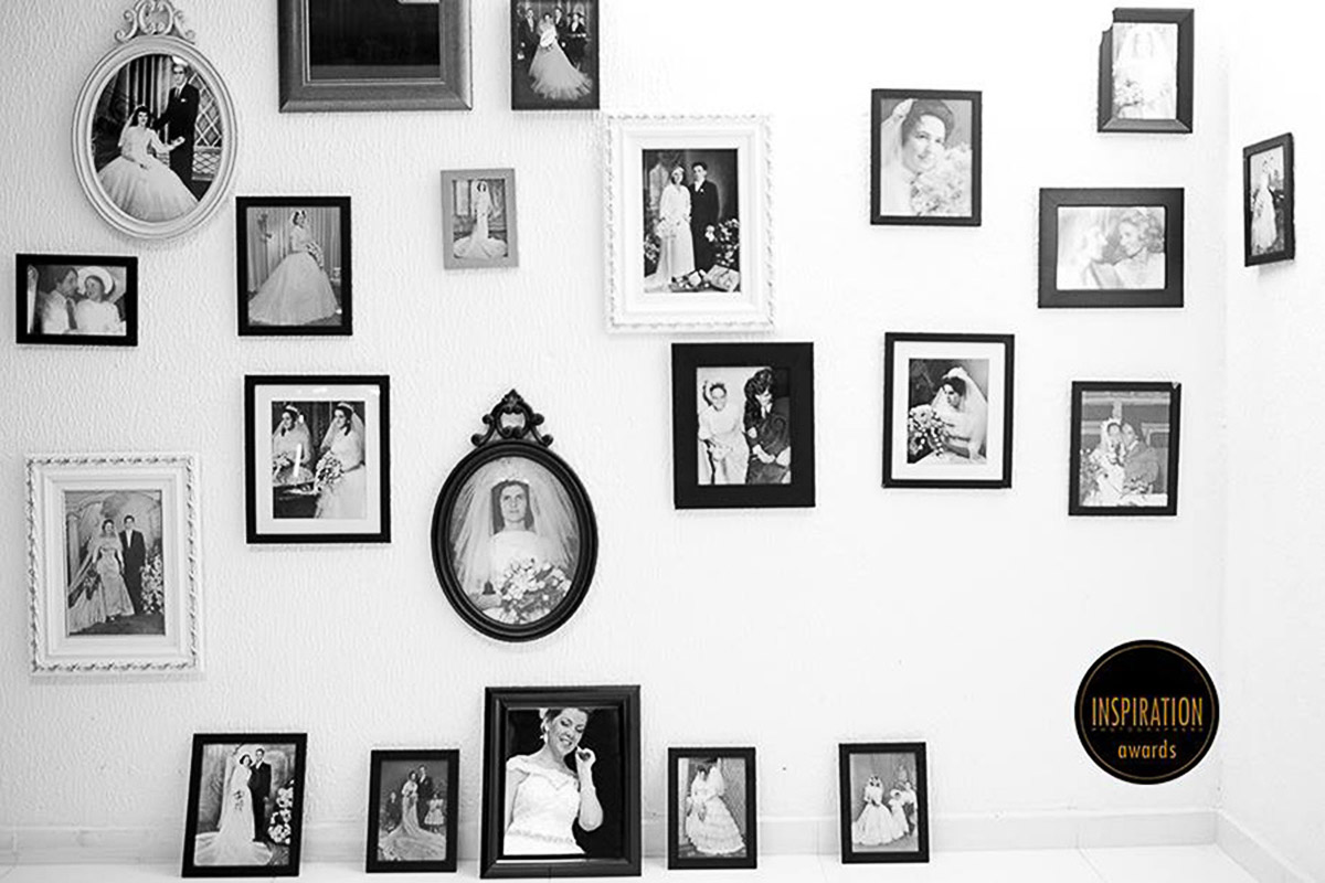 Noiva é fotografada entre varios porta retratos, refletida em um espelho, a imagem faz parecer que a noiva é uma imagem de um outro porta retrato, premiada duas vezes.