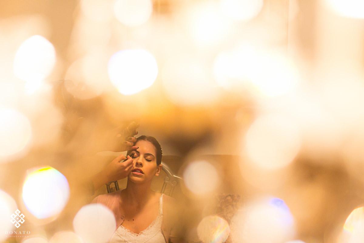 Making da noiva, imagem entre as luzes do lustre bem criativa.
