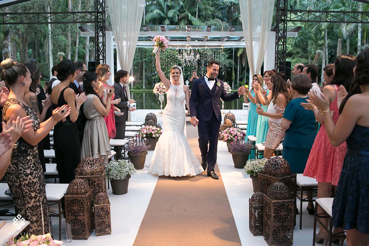 noivos saem alegres com braços erguidos em comemoração do sucesso do casamento.