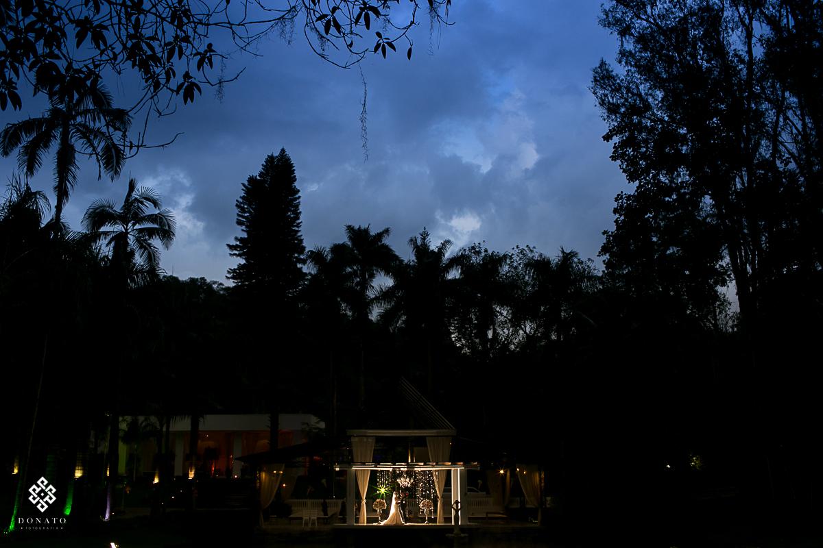 foto criativa, feita de longe mostrando todo o cenário da fazenda 7 lagoas, e com os noivos em detalhe ao meio, para completar um lindo céu azul.
