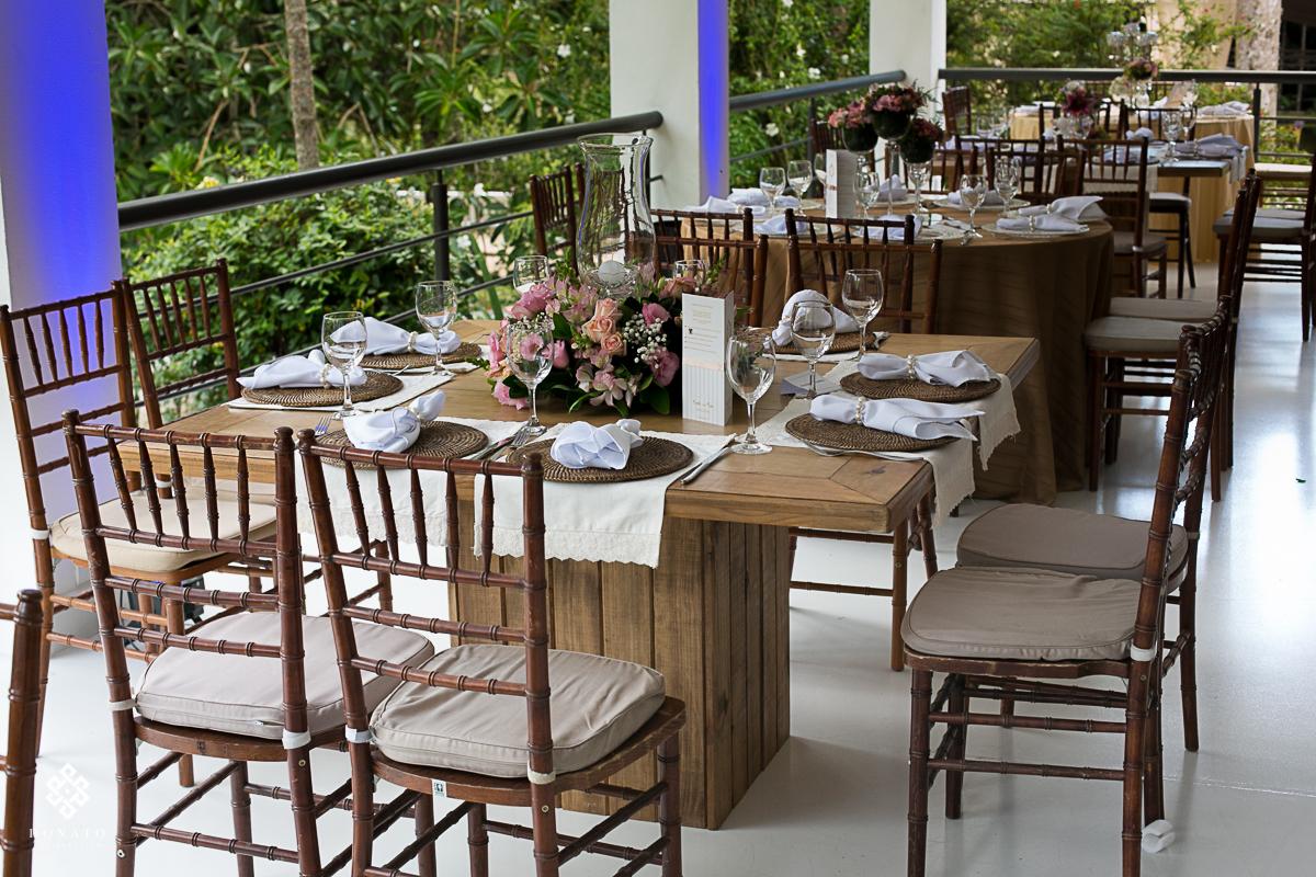 decoração com detalhes em rosa, com mesa de madeira e cadeiras que combinam, tudo isso decorando o ambiente do casamento na fazenda 7 lagoas sp.