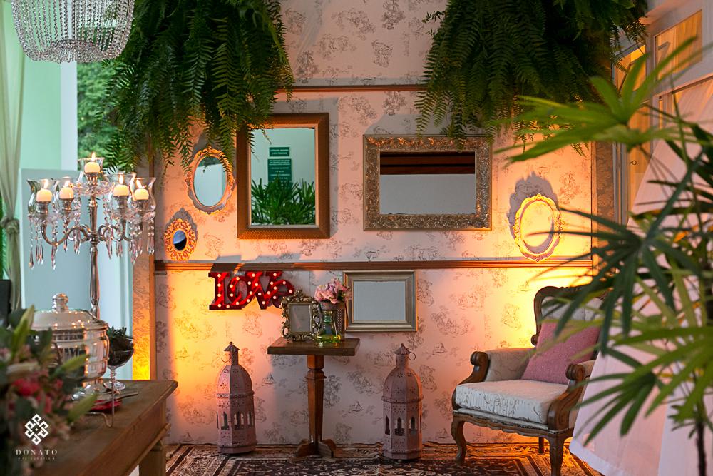 detalhes em quadros e espelhos na parede, samambaias fazem parte da decoração penduradas no teto.