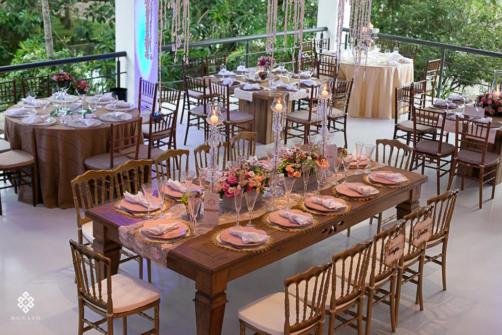 mesa compartilhada em madeira, com decoraçao em cor rosa, e guardanapos de pano brancos.