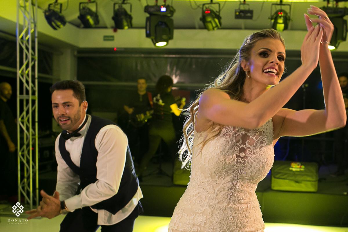 noiva dança, colocando o corpo para o lado direito e o noivo para o lado esquerdo, esta foto passa muita energia e diversao.