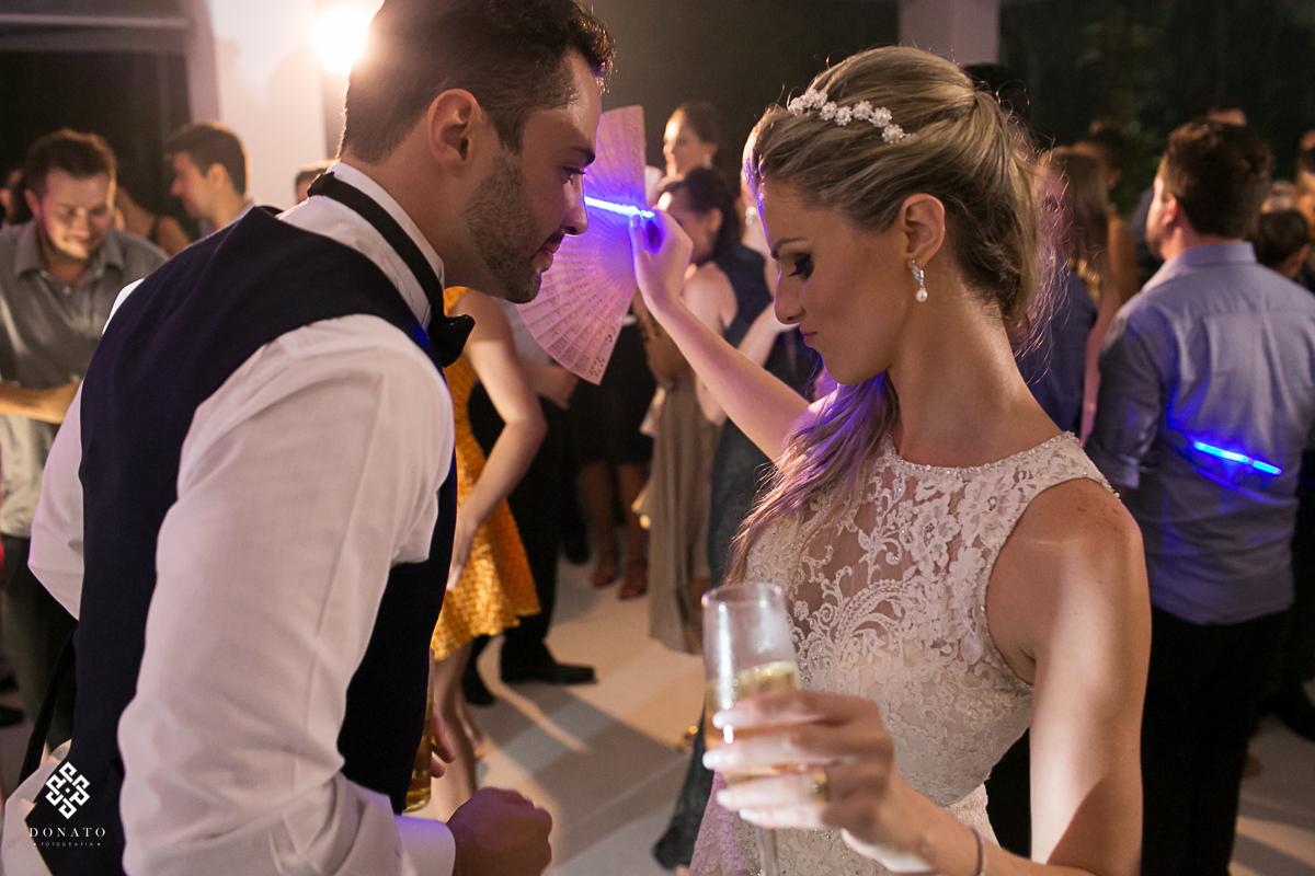 noivos sse divertem na pista de dança, a noiva esta tomando um drink bonito e o noivo se diverte junto.