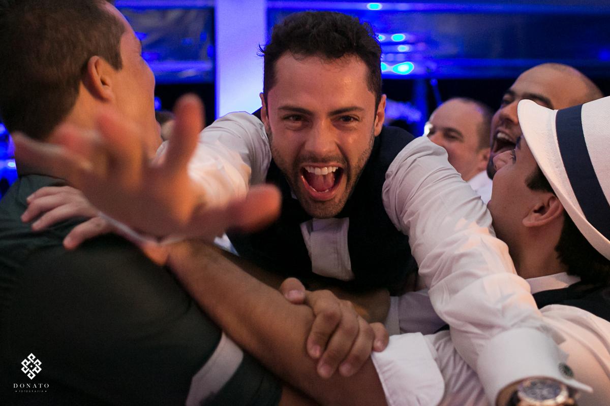 imagem do noivo caindo no braço dos amigos, olhando direto para camera com um lindo sorriso de alegria.