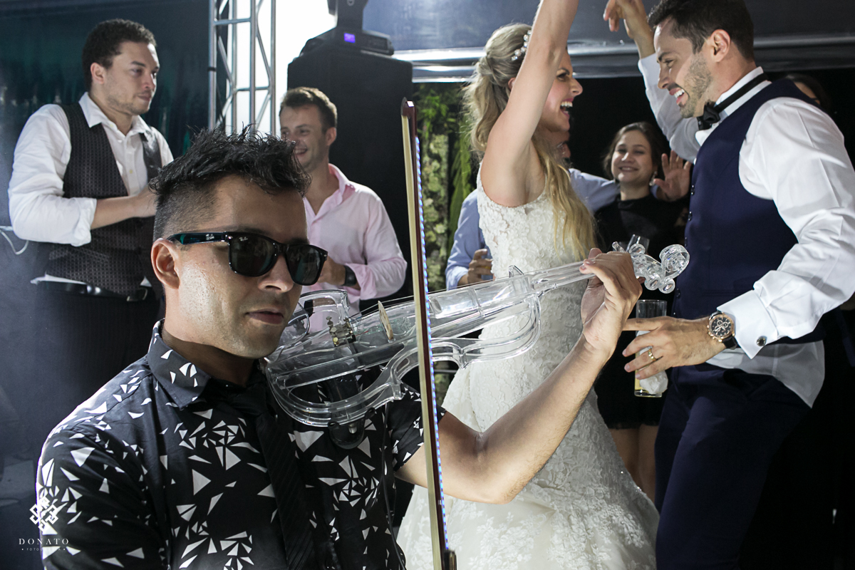 musico toca violino junto ao DJ, a noiva e noivo dançam ao fundo se divertindo muito.