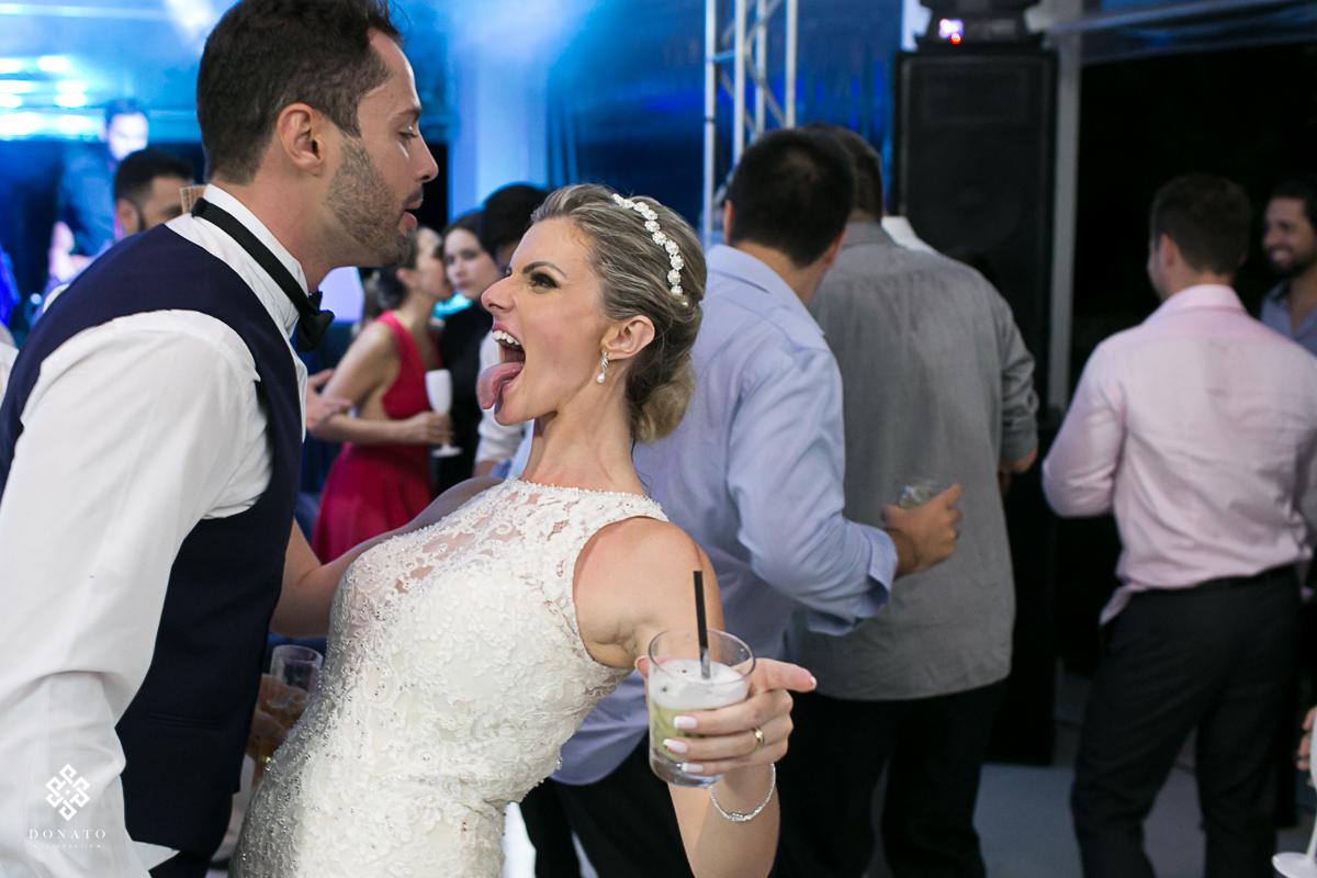 noiva mostra a língua enquanto dança com o noivo.