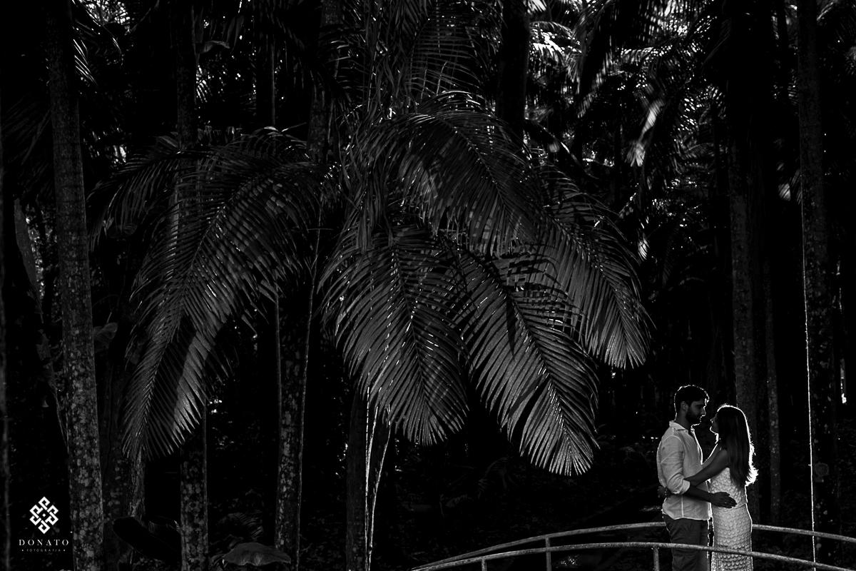 Noivos sao fotografados na ponte em frente ao lago da fazenda.