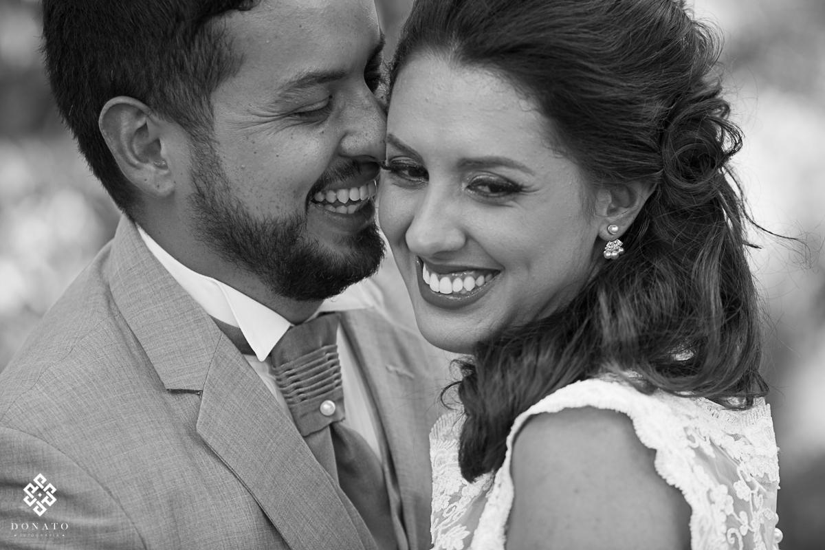 sorriso lindo da noiva enquanto o noivo da um beijo no rosto dela.